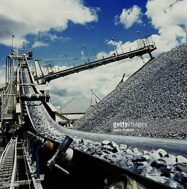 Rocks on conveyor belt dropping onto large rock pile (cross-processed)