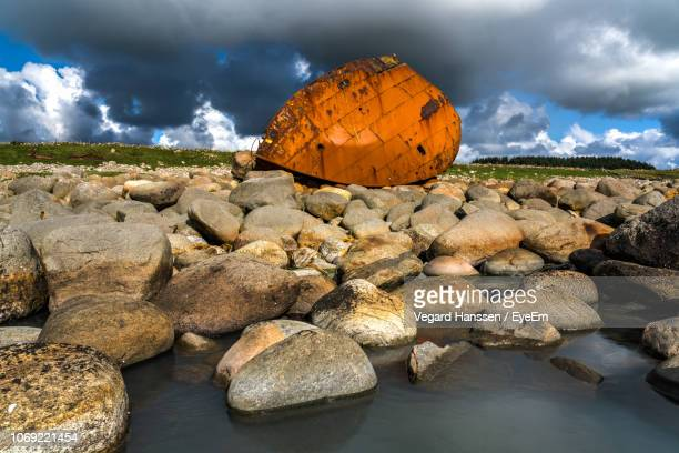 Rocks On Riverbank Against Sky