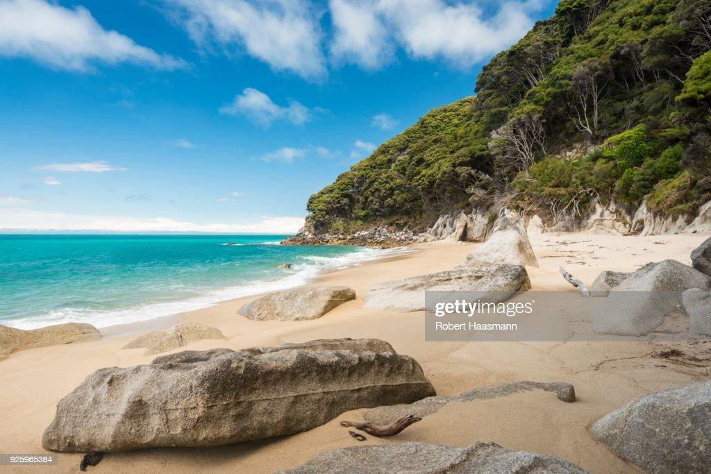 Rocks on sandy beach with tropical vegetation, Tonga Quarry, Tonga Bay, Abel Tasman National Park, Tasman Region, Southland, New Zealand : Stock-Foto