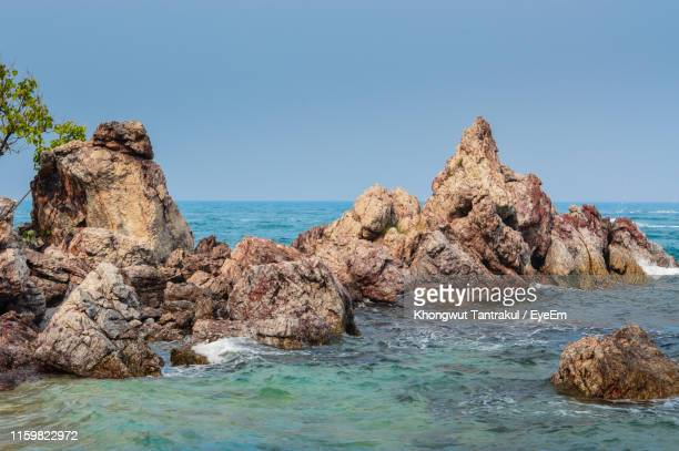 rocks on sea shore against clear blue sky - stack rock stock pictures, royalty-free photos & images