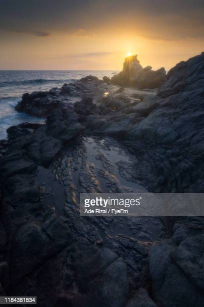 rocks on sea shore against sky during sunset - ade rizal stock photos and pictures