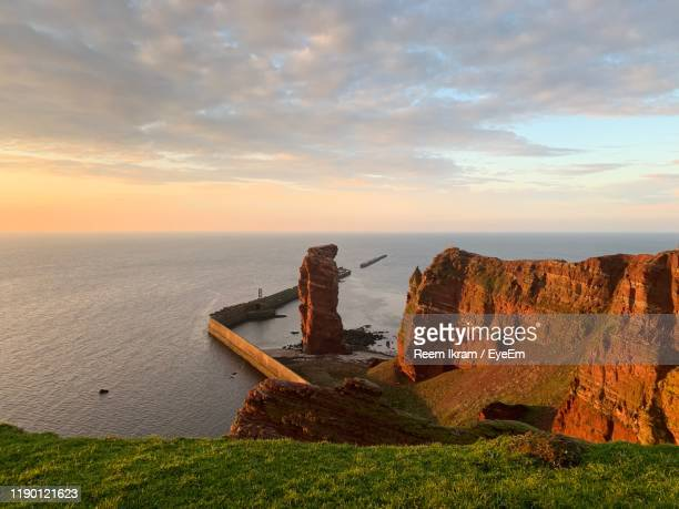 rocks on sea shore against sky during sunset - helgoland stock pictures, royalty-free photos & images