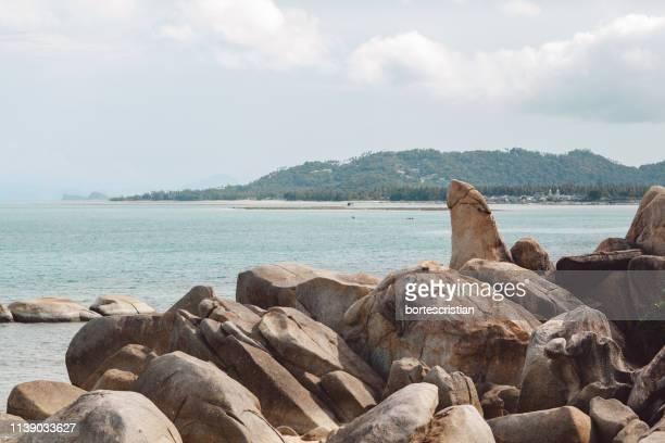 rocks on sea shore against sky - bortes cristian stock-fotos und bilder