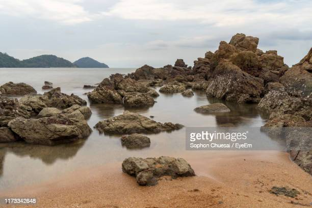 rocks on sea shore against sky - chanthaburi sea stock pictures, royalty-free photos & images