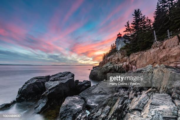 rocks on shore against sky during sunset - maine stock pictures, royalty-free photos & images