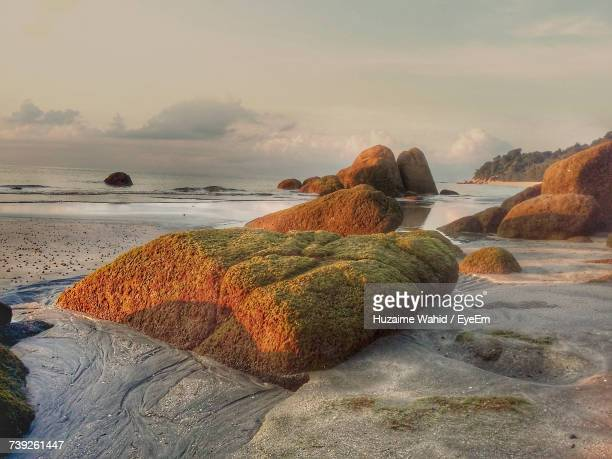 Rocks On Shore At Beach Against Sky During Sunset
