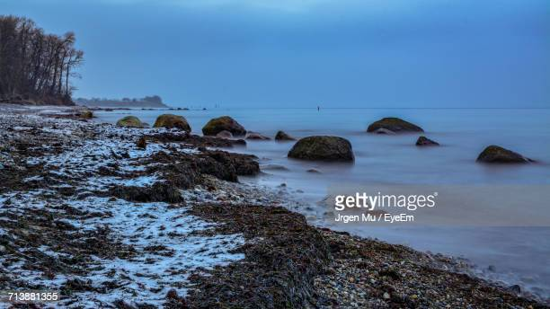 rocks on shore at beach against sky - fehmarn stock-fotos und bilder