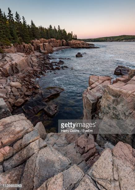 rocks on shore by sea against sky - rocky coastline stock pictures, royalty-free photos & images