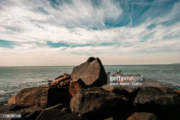 rocks on shore by sea against sky - redondo beach california stock pictures, royalty-free photos & images