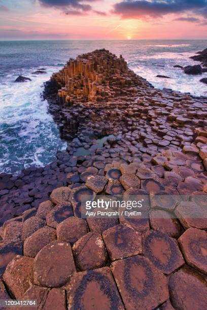rocks on shore during sunset - giant's causeway stock pictures, royalty-free photos & images