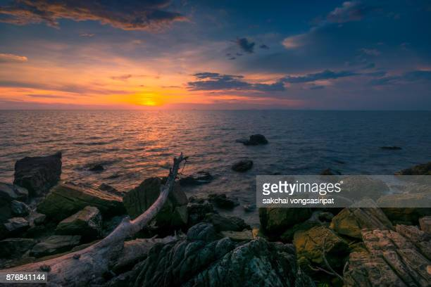 rocks on the beach against dramatic sky during sunset - chanthaburi sea stock pictures, royalty-free photos & images