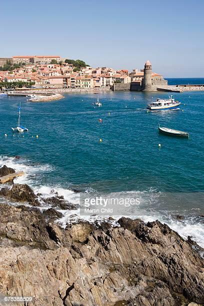 rocks on the coast and eglise notre-dame-des-anges, collioure, pyrenees-orientales, cote vermeille, france, europe - collioure photos et images de collection