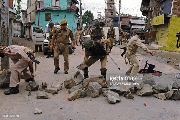 Rocks placed by Kashmiri protesters to block a road are removed by police during clashes in Srinagar on July 30, 2010. Violent clashes between...