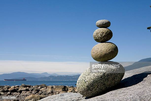 rocks stacked on beach, english bay, vancouver bc - english bay stock photos and pictures