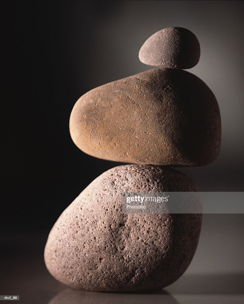 Rocks stacked on each other while standing on a reflective surface with a gray and black background : Foto de stock