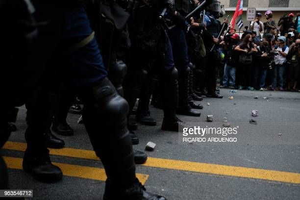 Rocks thrown by protesters are seen on the road in front of a riot line during a May Day protest against pension cuts school closures and slow...