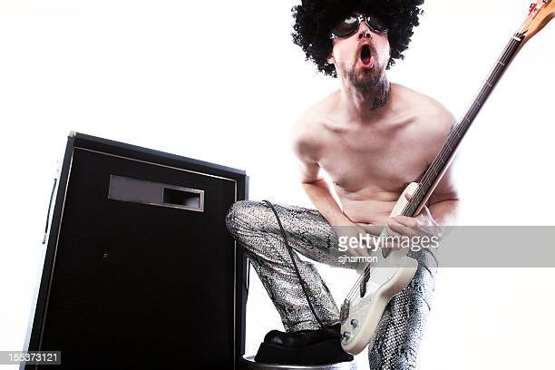rockstar in silver pants rocking with white electric guitar, amplifier - man in tight pants stock photos and pictures
