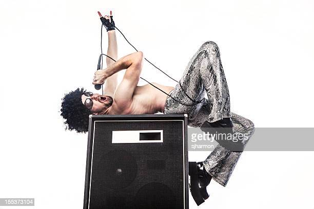 rockstar man in silver pants rocking with microphone, amplifier - man in tight pants stock photos and pictures