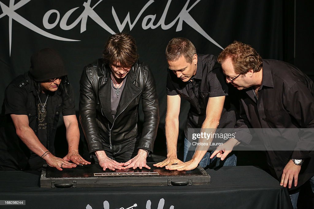 Rockwalk director Dave Weiderman (R) assists (2L-R) Bassist Robby Takac, vocalist / guitarist John Rzeznik and drummer Mike Malinin of Goo Goo Dolls as they are inducted into Guitar Center's historic RockWalk at Guitar Center on May 7, 2013 in Hollywood, California.