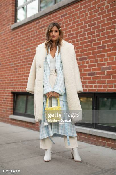 Rocky Barnes is seen on the street during New York Fashion Week AW19 wearing Jonathan Simkhai baby blue check outfit with white fur coat and yellow...