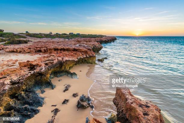 rocky beach at sunset, western australia. - western australia stock photos and pictures
