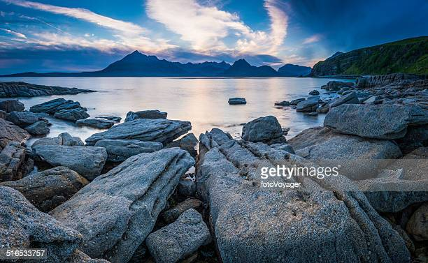 Rocky beach blue ocean sunset dramatic mountain peaks Highlands Scotland
