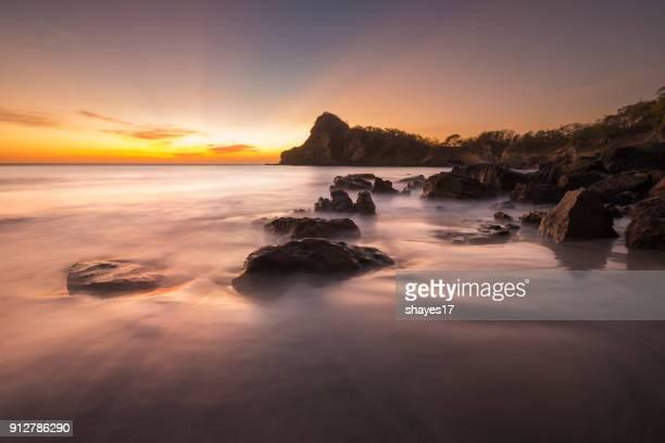 puesta de sol de playa rocosa marina - nicaragua fotografías e imágenes de stock
