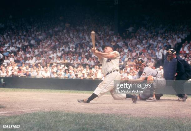 Rocky Bridges of the Detroit Tigers swings at the pitch as catcher Gus Triandos of the Baltimore Orioles is behind the plate during an MLB game on...