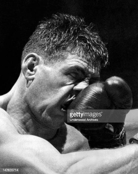 Rocky Castellani takes a right in the nose from Pierre Langlois of France in their middleweight match at Madison Square Garden New York New York...