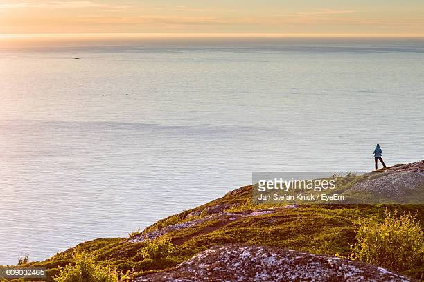 Rocky Cliff Against Seascape During Sunset