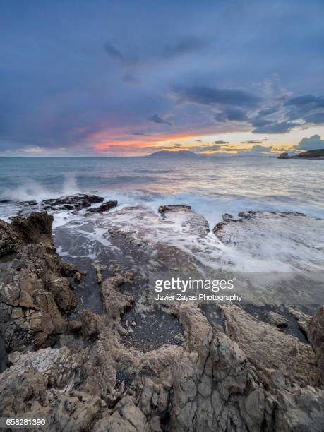 rocky cliff against seascape during sunset - mojado stock pictures, royalty-free photos & images