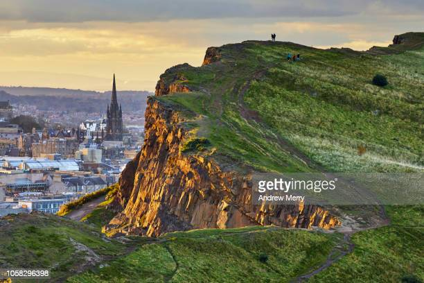 rocky cliffs of salisbury crags in holyrood park with edinburgh city the in background at sunset - schotse cultuur stockfoto's en -beelden