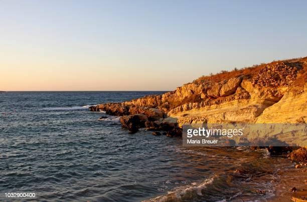 rocky coast, sunset, hersonissos, crete, greece - hersonissos photos et images de collection