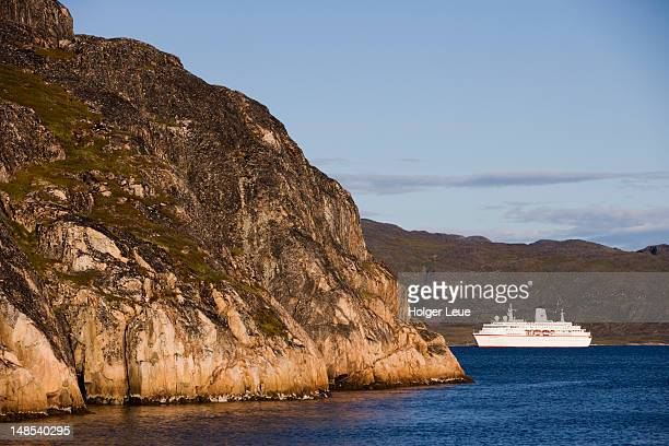 rocky coastline and cruiseship ms deutschland. - ms deutschland cruise ship stock photos and pictures
