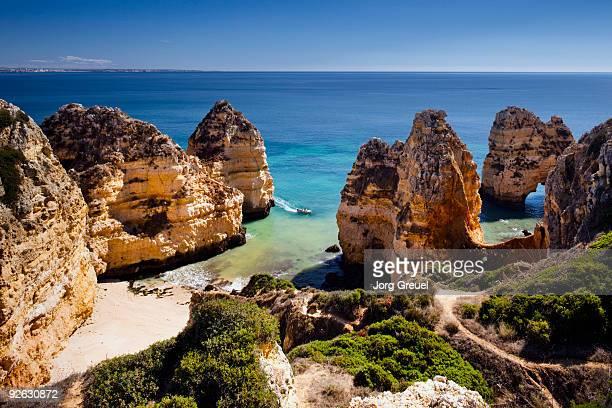 rocky coastline near ponta da piedade - ポルトガル ファロ県 ストックフォトと画像