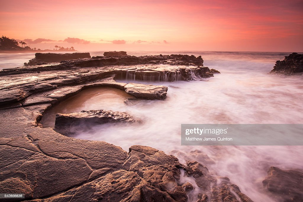 Rocky Hawaiian shore with pink sunrise and misty water : Stock Photo