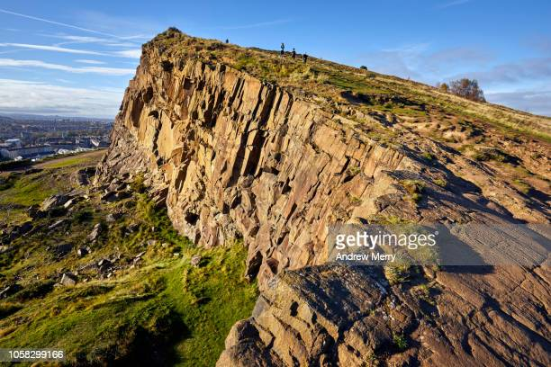 rocky landscape of salisbury crags, holyrood park with edinburgh city the in background at sunset - scogliera foto e immagini stock