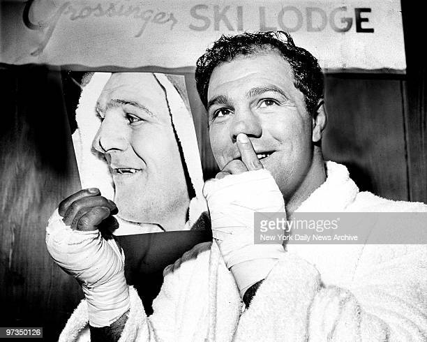 Rocky Marciano looks at picture of himself with split nose he received in fight with Ezzard Charles.