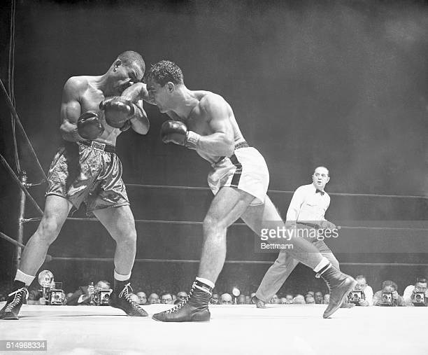 Rocky Marciano seems to have his elbow up against the face of ex-heavyweight champ Joe Louis during this hectic part of their scheduled ten-round...