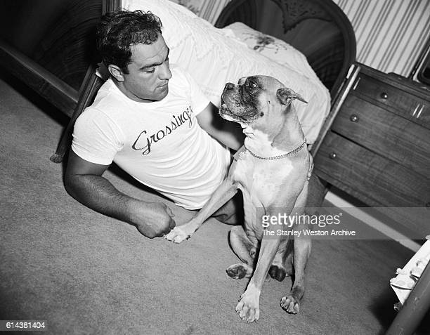 Rocky Marciano takes a moment to spend some time with his dog in Grossingers New York September 1954