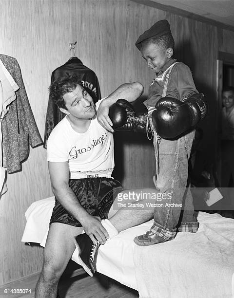 Rocky Marciano takes some time to entertain a young fan during his time training for his title defense against Archie Moore at Grossingers New York...