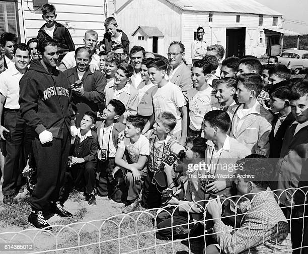 Rocky Marciano takes some time to talk to a group of young fans visiting from camp during his time training for his title defense against Archie...