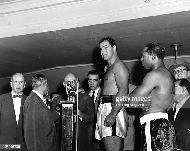 Rocky Marciano weighsin as Archie Moore looks on before the fight at Yankee Stadium on September 211955 in Bronx New York Rocky Marciano won the...