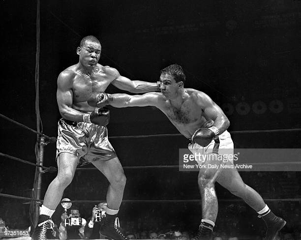 Rocky Marciano's eyes glint confidently after he drives a tremendous right to jaw that practically paralyzes Joe Louis in the eighth round at Garden...
