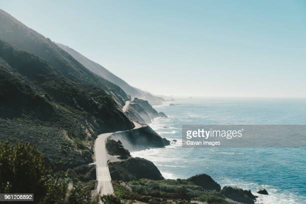 rocky mountain by sea against clear blue sky - big sur stock pictures, royalty-free photos & images
