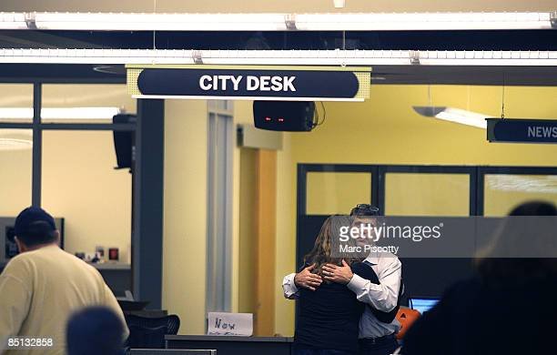 Rocky Mountain News editor publisher and president John Temple hugs Judy DeHaas a staff photographer at the paper in the newsroom February 26 2009 in...