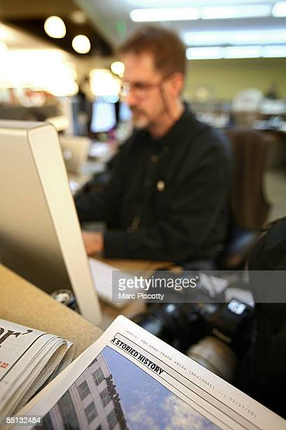 Rocky Mountain News picture editor Mark Holm works at the picture desk as a page from tomorrow's final edition still in the mockup stages sits on the...