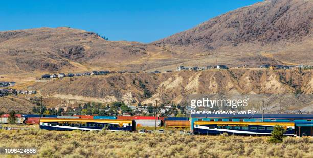 Rocky Mountaineer passes a freight train in the rugged mountainous landscape of British Columbia, at Kamloops, Canada, North America.