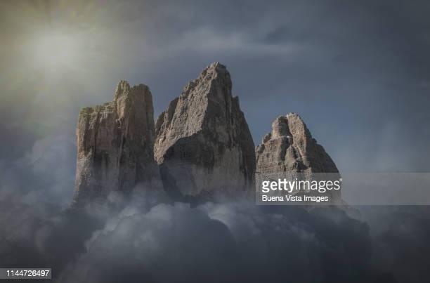 rocky mountains emerging from clouds - トレチーメディラバレード ストックフォトと画像