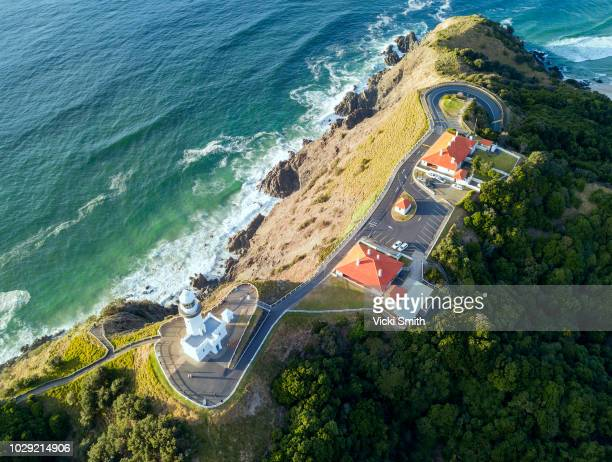 rocky outcrop into ocean with lighthouse and road